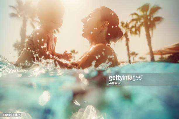 mother with child having fun in pool at sunset - tourist resort stock pictures, royalty-free photos & images