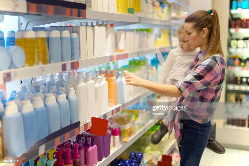 Mother with child shopping for hygiene products : Stock Photo