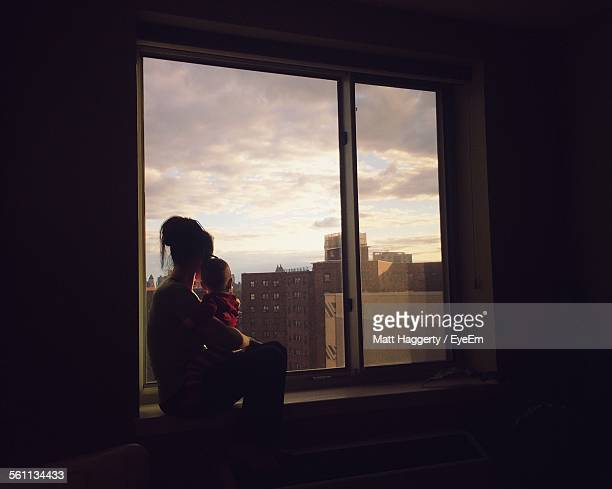 mother with child sitting in front of window - front view photos et images de collection