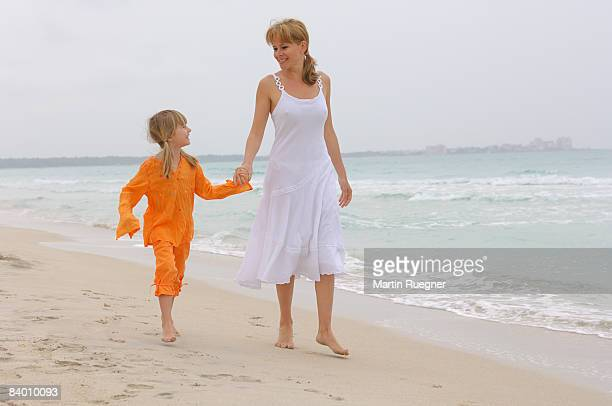 mother (25-30) with child (5 years) walking beach. - 25 29 years stock pictures, royalty-free photos & images