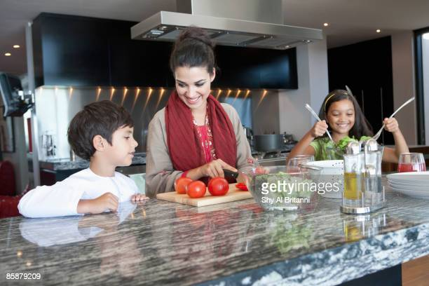 Mother with children cooking in kitchen.
