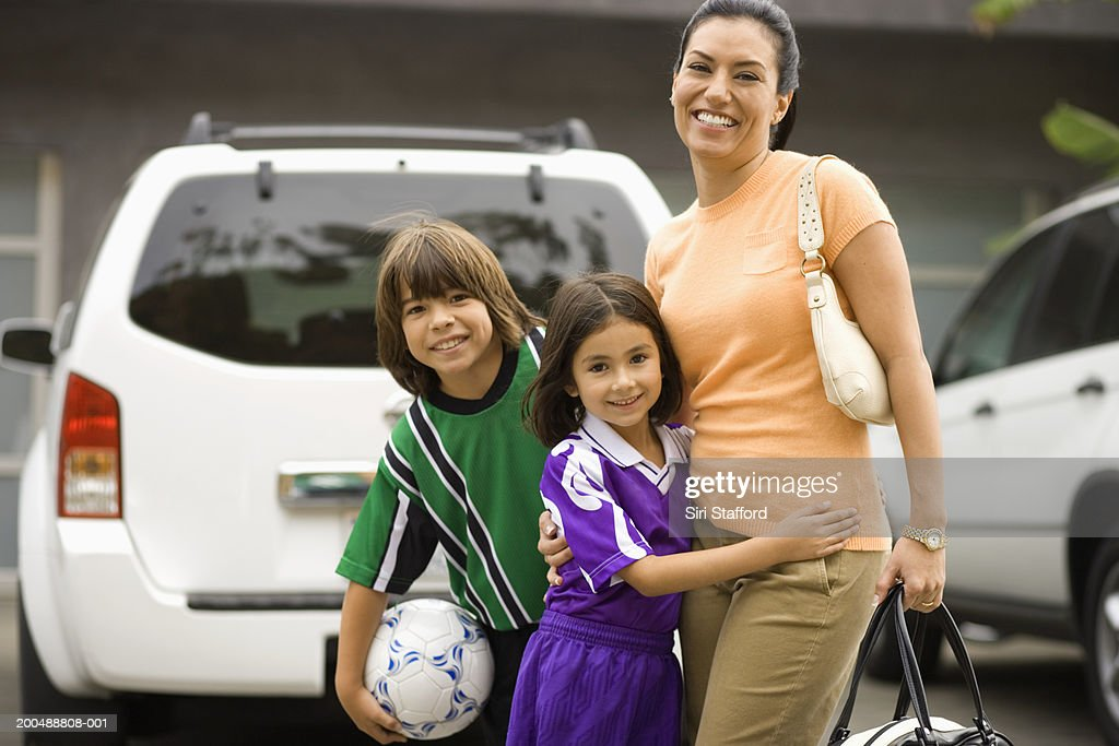 Mother with children (6-10) dressed in soccer uniforms : Stock Photo