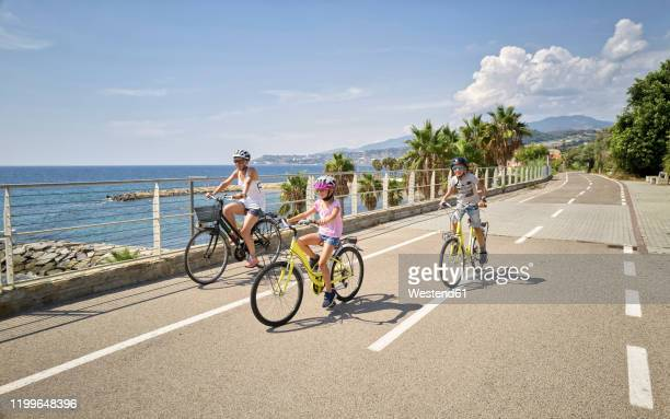 mother with children during bicycle tour between san lorenzo and san remo, italy - liguria foto e immagini stock