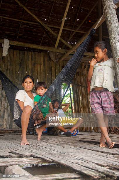 A mother with children in a house on stilts in a village along the Maranon River in the Peruvian Amazon River basin near Iquitos
