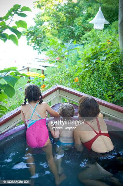 mother with children in hot tub looking at lake - girls in hot tub stock photos and pictures