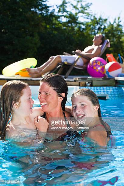 Mother with children in swimming pool