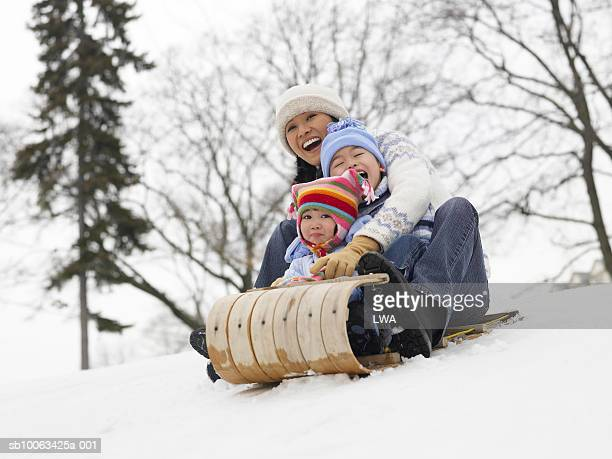 mother with children (4-9) sledding down snowy hill - tobogganing stock pictures, royalty-free photos & images