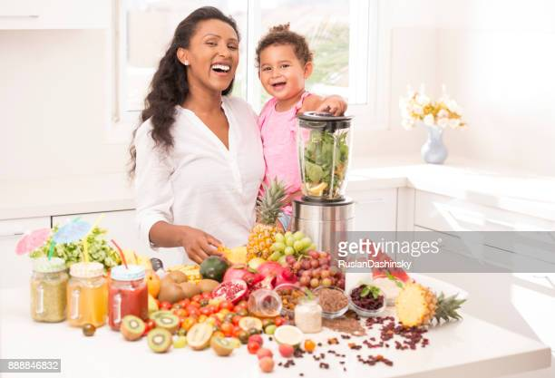 mother with daughter 2-3 years age making fruit juices at kitchen. - mint plant family stock pictures, royalty-free photos & images