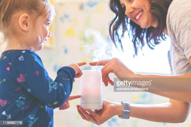 mother with daughter active at home experiencing quality life in bathroom preparing essential oil diffuser - essential oil stock pictures, royalty-free photos & images