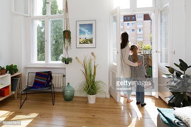 Mother with daughter at home standing at balcony door