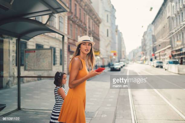 バス停で娘と母 - 待つ ストックフォトと画像