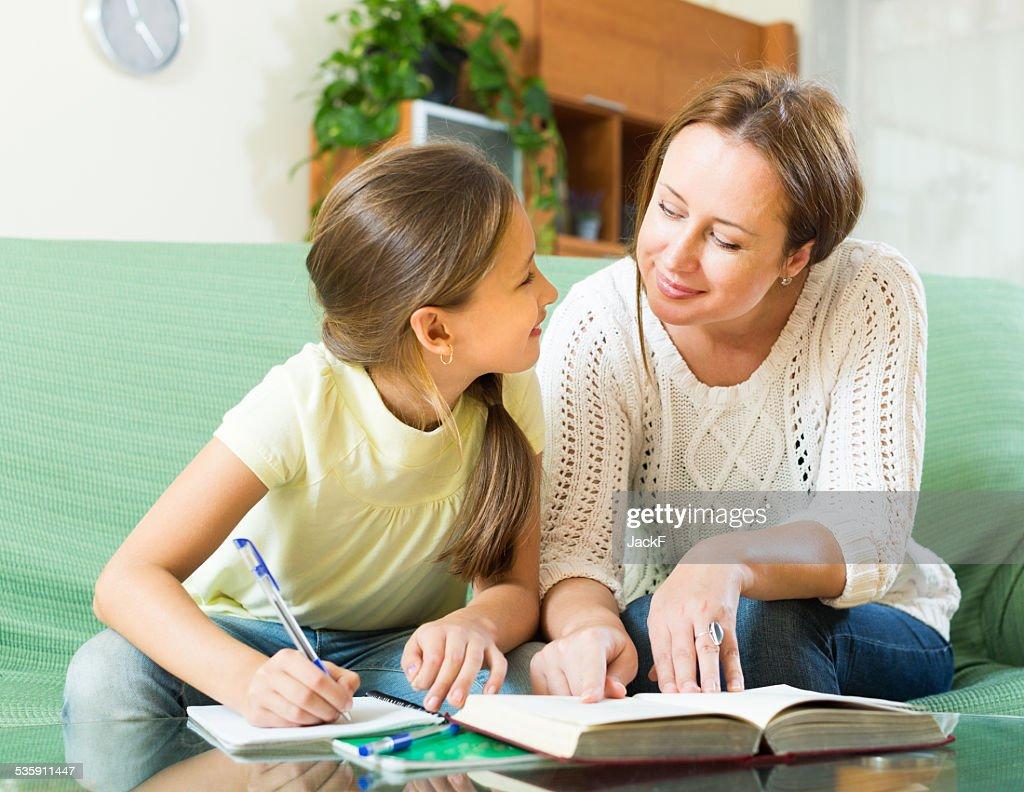 Madre con hija haciendo los deberes : Foto de stock