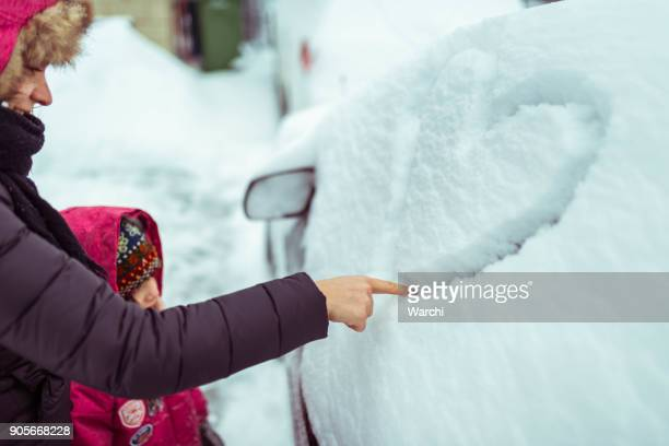 Mother with daughter drawing a heart shape on her husband's car covered in snow