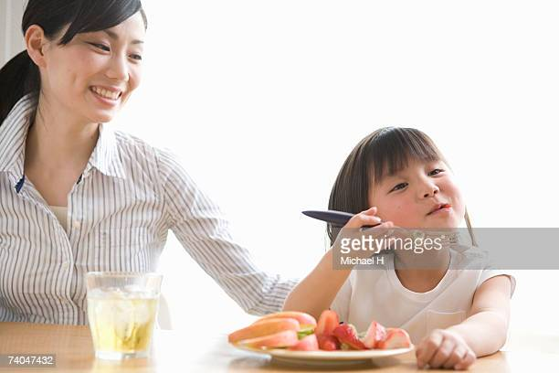 Mother with daughter (6-7) eating fruit in kitchen