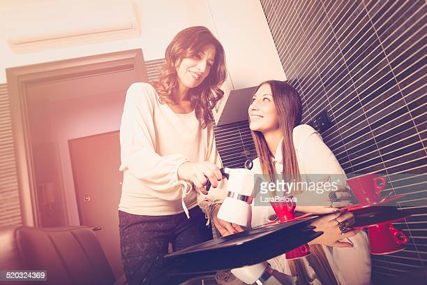 Mother with daughter enjoying a coffee for breakfast
