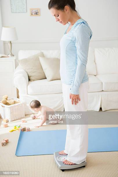 Mother with daughter (6-11 months) exercising and checking weight in living room