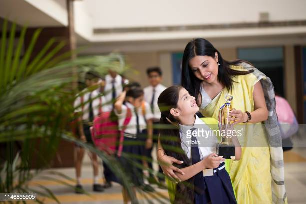 mother with daughter holding trophy at school - day stock pictures, royalty-free photos & images