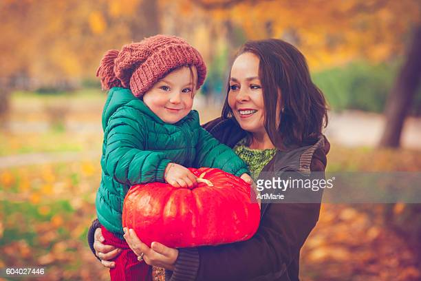 Mother with daughter in autumn with pumpkin