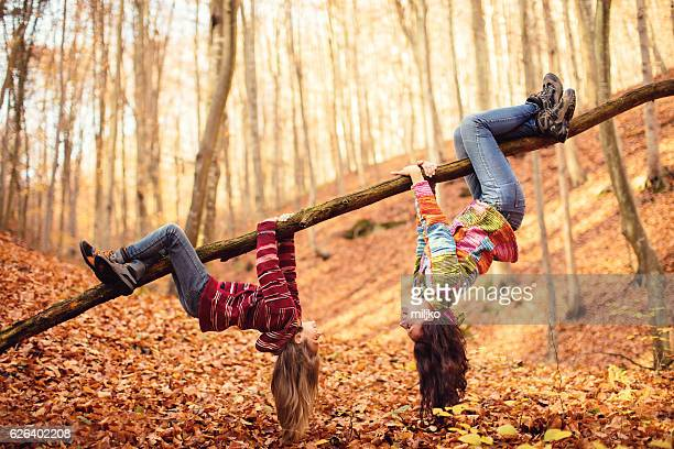 mother with daughter in autumn wood - op z'n kop stockfoto's en -beelden
