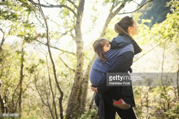 Mother with daughter in baby carrier trekking in forest