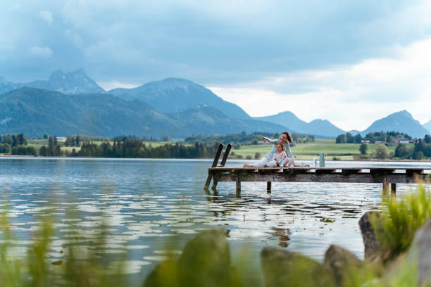Mother with daughter looking at view while sitting on jetty over lake against sky