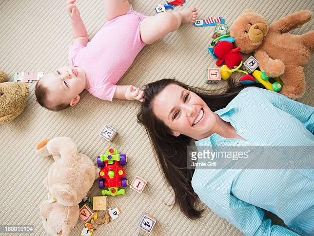 Mother with daughter (6-11 months) lying on floor