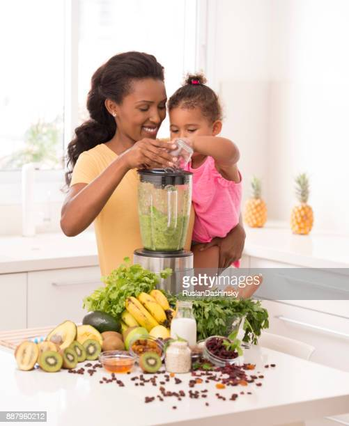 mother with daughter making fresh smoothie in the kitchen - mint plant family stock pictures, royalty-free photos & images