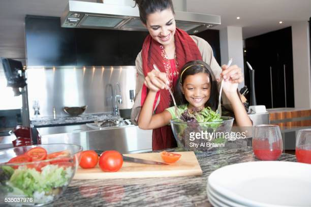 Mother with daughter mixing salad in bowl
