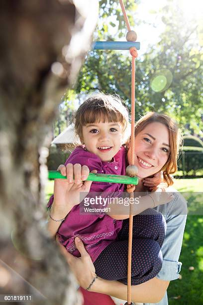 Mother with daughter on rope ladder in garden