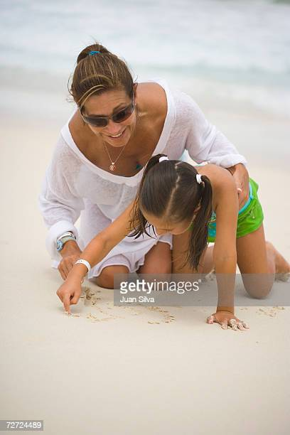 Mother with daughter (5-6) playing in sand at beach, smiling