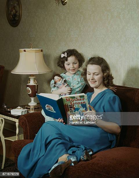 mother with daughter reading book and sitting in sofa  - {{ contactusnotification.cta }} stock pictures, royalty-free photos & images