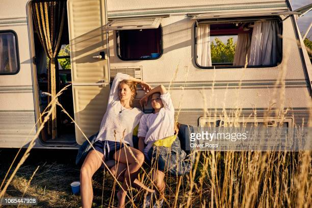 mother with daughter relaxing at a caravan - camper trailer stock pictures, royalty-free photos & images