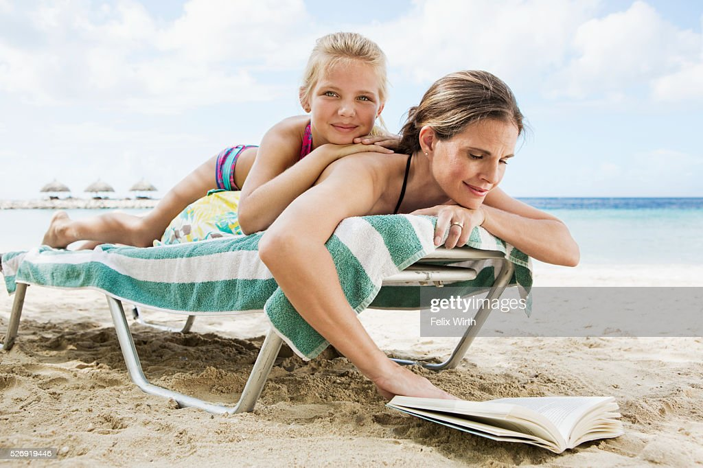 Mother with daughter (10-12) relaxing on deckchair on beach : Stock-Foto