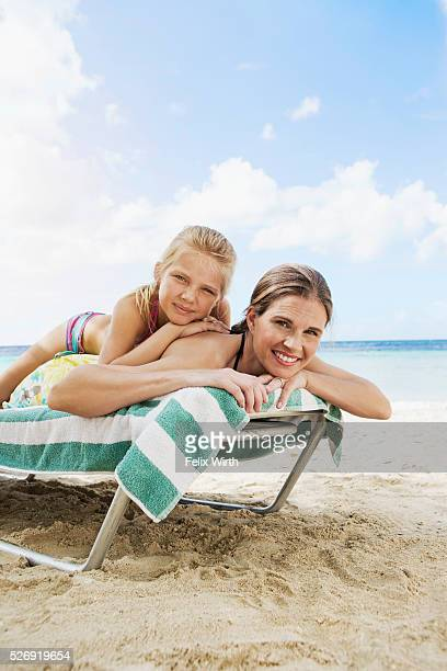 Mother with daughter (10-12) relaxing on deckchair on beach