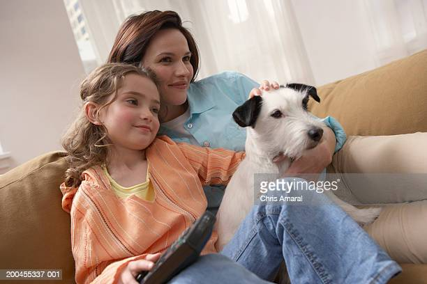 mother with daughter (8-10) relaxing on sofa with dog - einzelnes tier stock-fotos und bilder