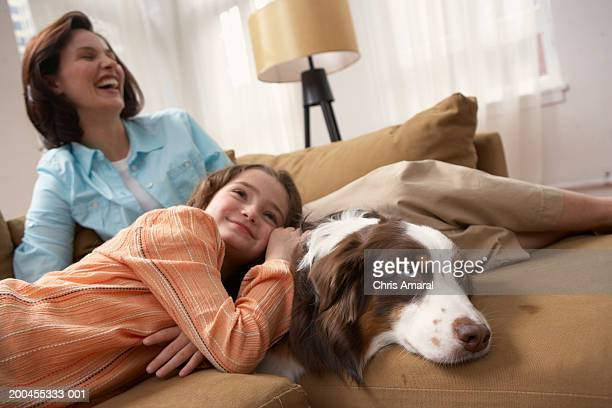 Mother with daughter (8-10) relaxing on sofa with dog, smiling