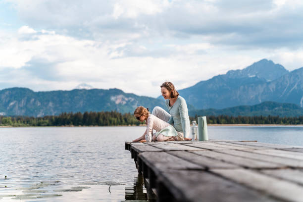 Mother with daughter sitting on jetty over lake against sky