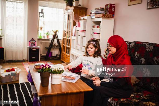 mother with daughter sitting on sofa - västra götaland county stock pictures, royalty-free photos & images