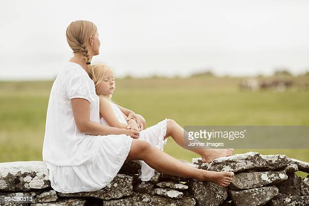 Mother with daughter sitting on stone wall