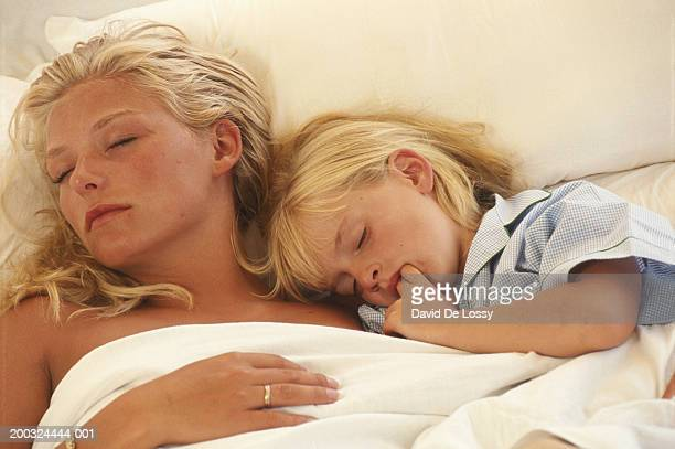 mother with daughter (6-7) sleeping on bed, elevated view - side by side stock photos and pictures