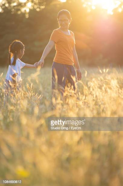 Mother With Daughter Standing Amidst Plants On Field During Sunset