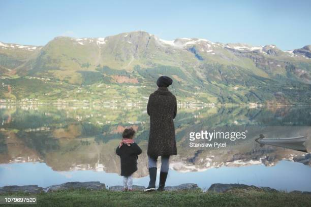Mother with daughter standing on lakes edge