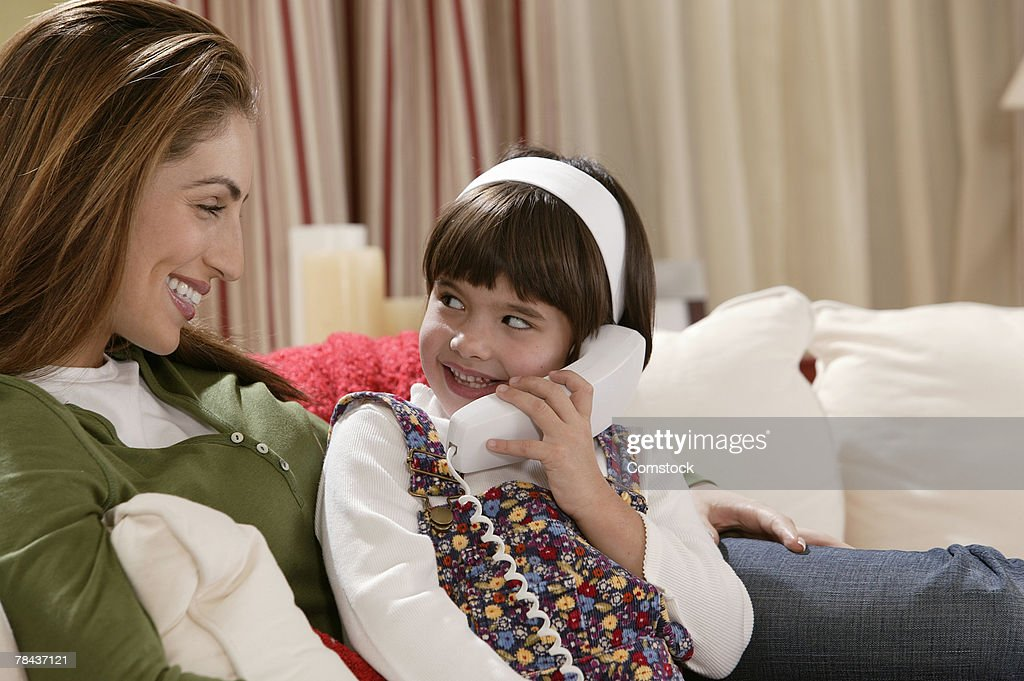 Mother with daughter talking on telephone : Stockfoto