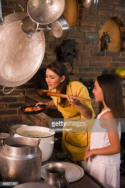 Mother with daughter tasting stew in kitchen , Colombia