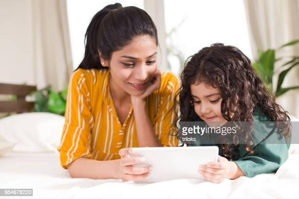 mother with daughter using digital tablet in bed - parent stock pictures, royalty-free photos & images