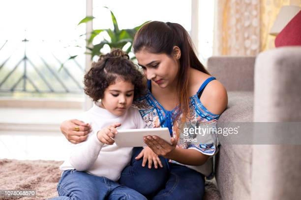 mother with daughter watching online media