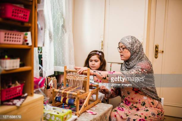 mother with daughter using loom - västra götaland county stock pictures, royalty-free photos & images