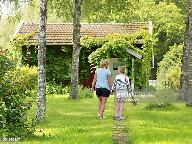 Mother with daughter walking in garden