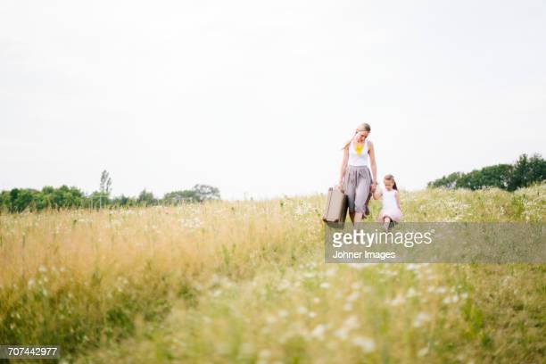 Mother with daughter walking in meadow