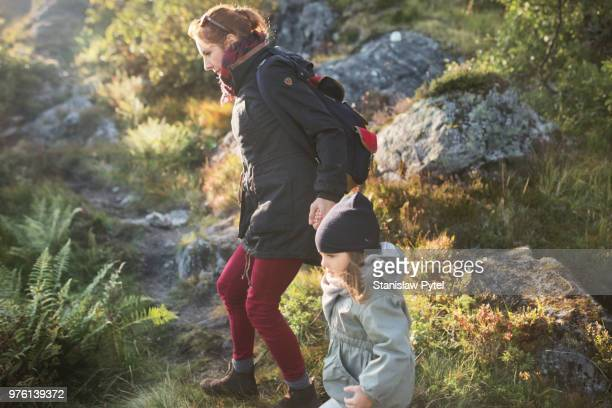 Mother with daughter walking in mountains at sunset